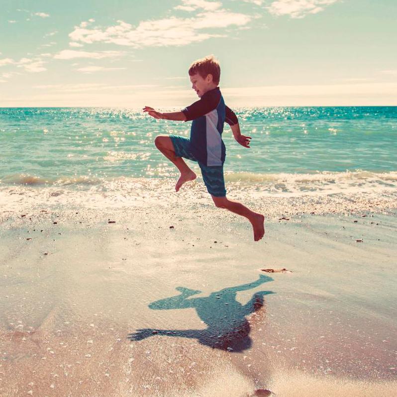 Niño saltando en la playa